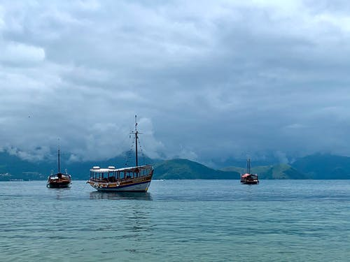 Picturesque view of vessels with wooden masts sailing on sea with rippled water behind mounts under sky with low clouds in overcast weather in afternoon