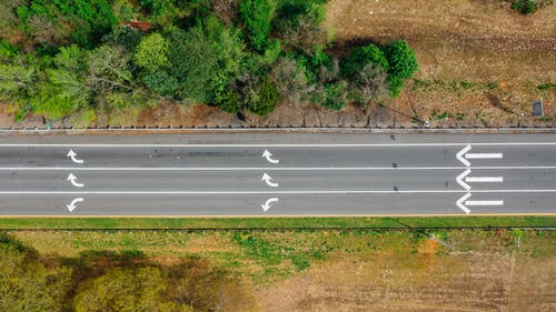 カラフルな木の近くに矢印の付いた道路の空撮