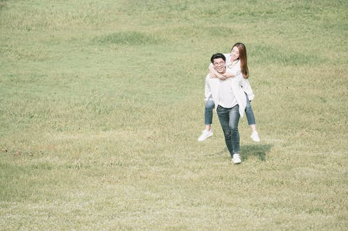 Happy Asian couple having fun in field