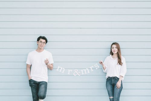 Content young Asian married couple in casual clothes holding garland with Mr and Mrs standing near blue wall and looking at camera