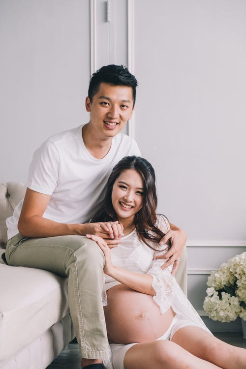 Cheerful expecting young couple sitting together in living room