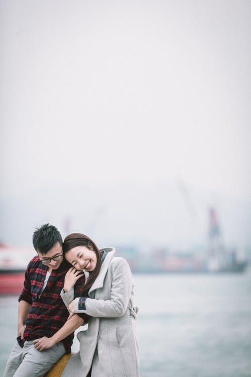Happy laughing Asian couple in casual outfits bonding while spending time together on urban waterfront