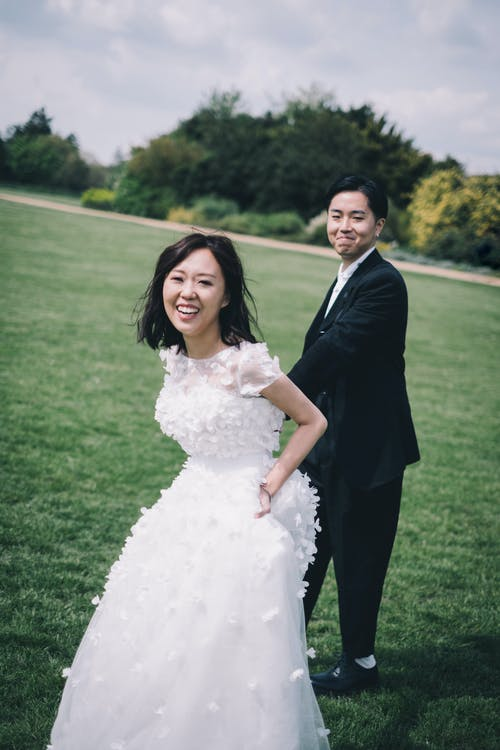 Joyful smiling young Asian couple in elegant wedding clothes holding hands and walking on grassy meadow in nature and looking at camera happily