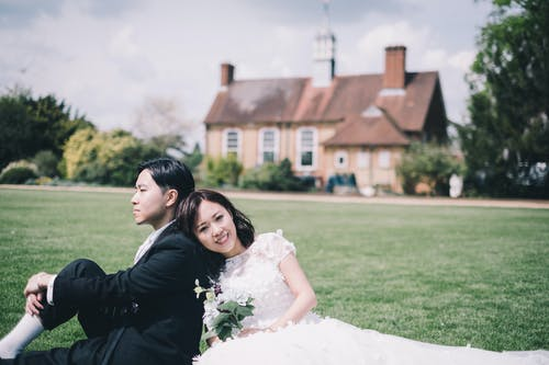 Content newlywed Asian couple resting on meadow against cozy mansion