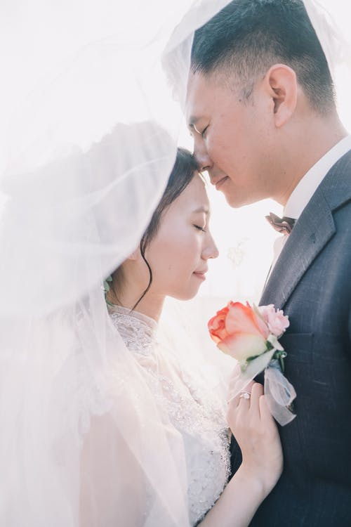 Side view serene Asian couple in exquisite wedding gowns standing under white veil with eyes closed face to face during wedding ceremony