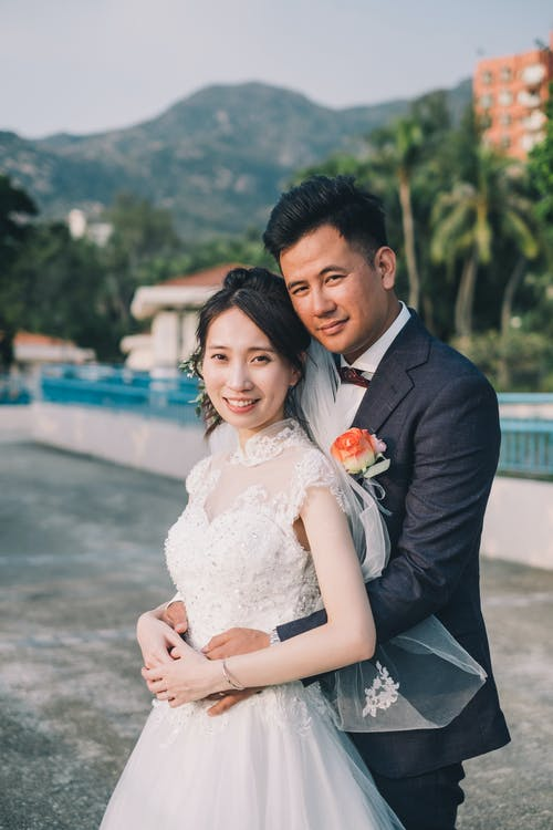 Newlywed Asian couple embracing in tropical park