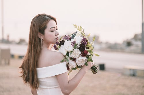 Side view of young romantic Asian bride in elegant white dress smelling beautiful bouquet of fresh delicate flowers during wedding wedding celebration near river