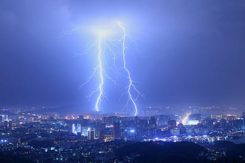 Breathtaking thunderstorm with lightning bolts over modern illuminated city at night with purple sky