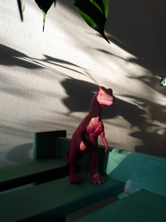 Pink Dinosaur Action Figure on Green Table