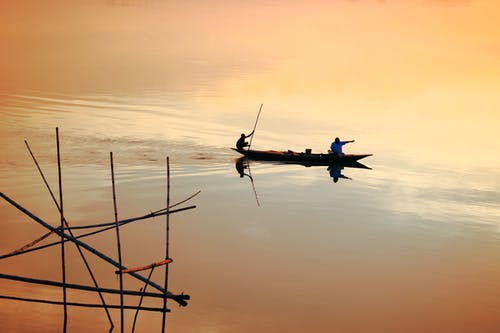 Silhouettes of unrecognizable men floating in traditional fishing boat against amazing sunset sky reflecting in calm water of sea