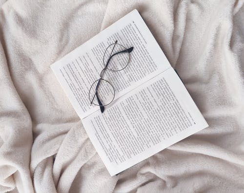 Opened textbook and eyeglasses on soft bed