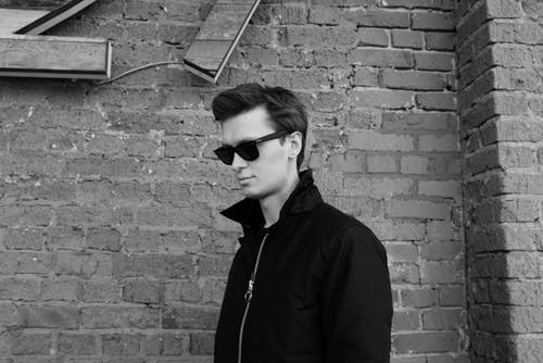 Calm man standing near brick wall on street