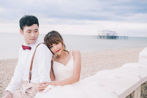 Happy young Asian bride in white dress cuddling with elegant groom during wedding celebration on sea sandy beach