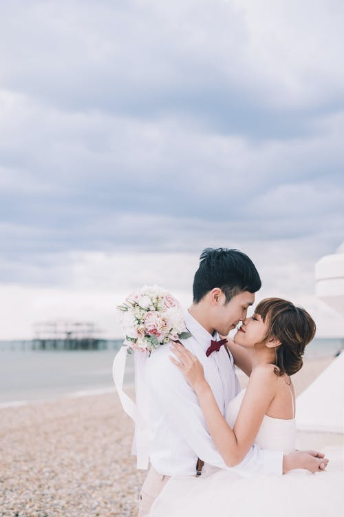 Side view of happy newlywed Asian couple hugging each other and kissing on sandy beach during wedding celebration at seaside