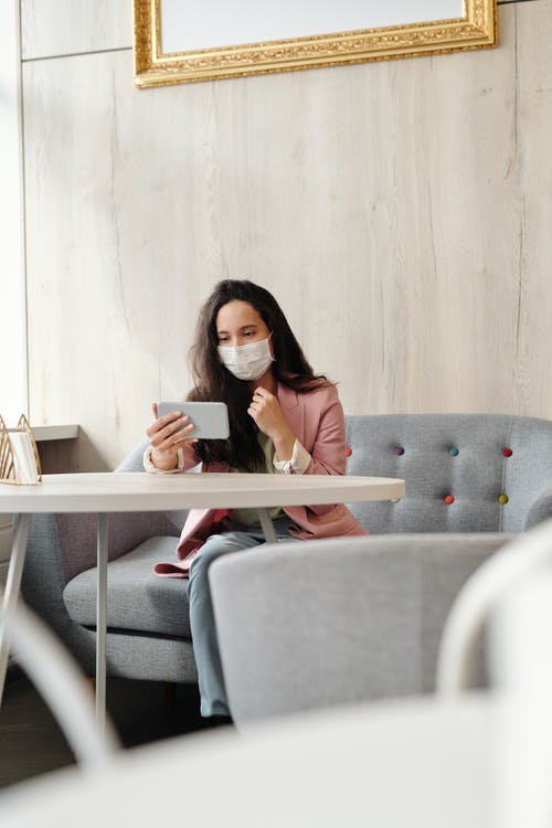 Woman Wearing A Face Mask While Sitted Using Her Phone