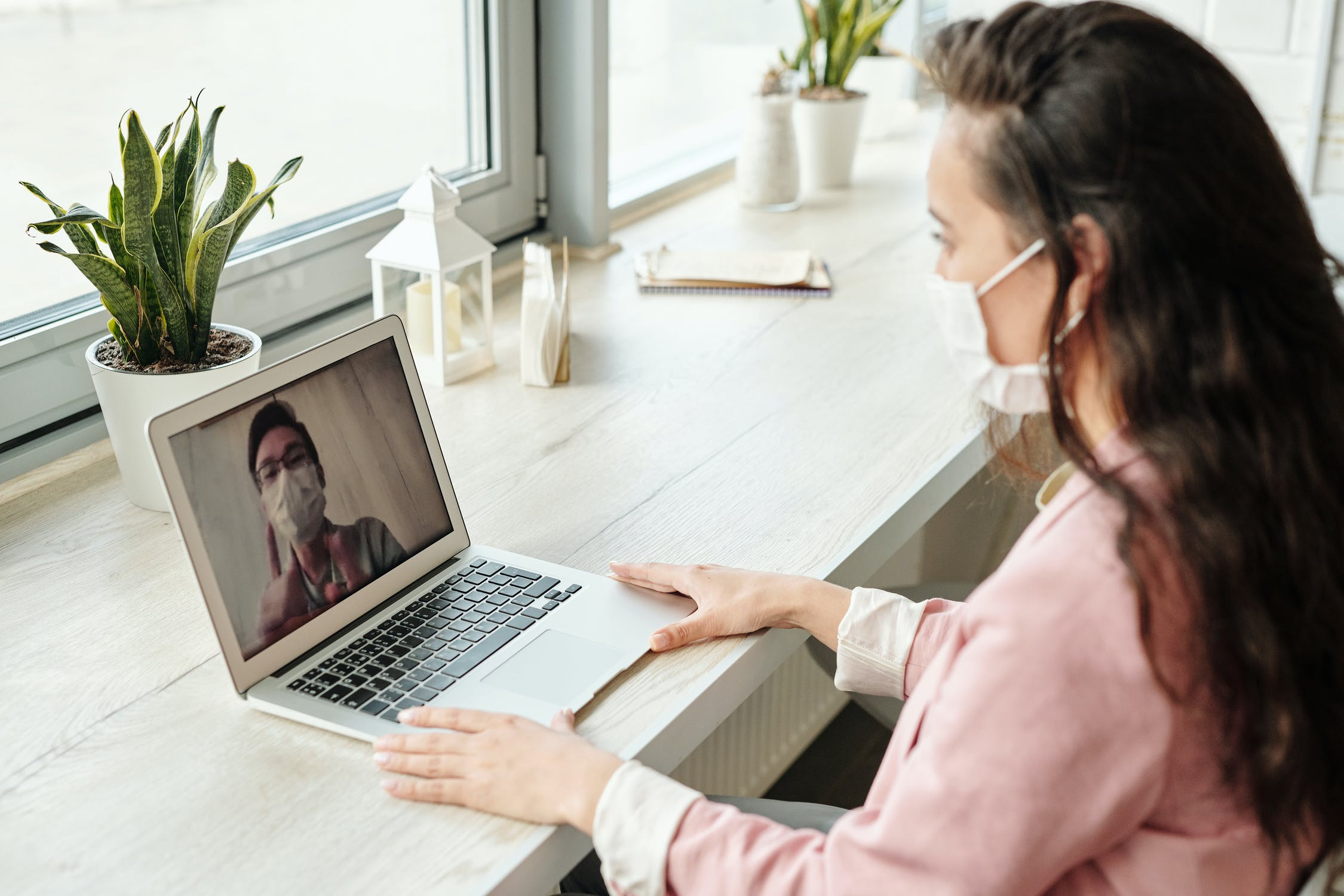 A woman wearing a face mask speaking to a man via a laptop video conference
