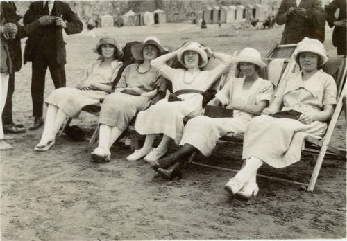 Foto En Escala De Grises De Mujeres Sentadas En Una Silla Plegable