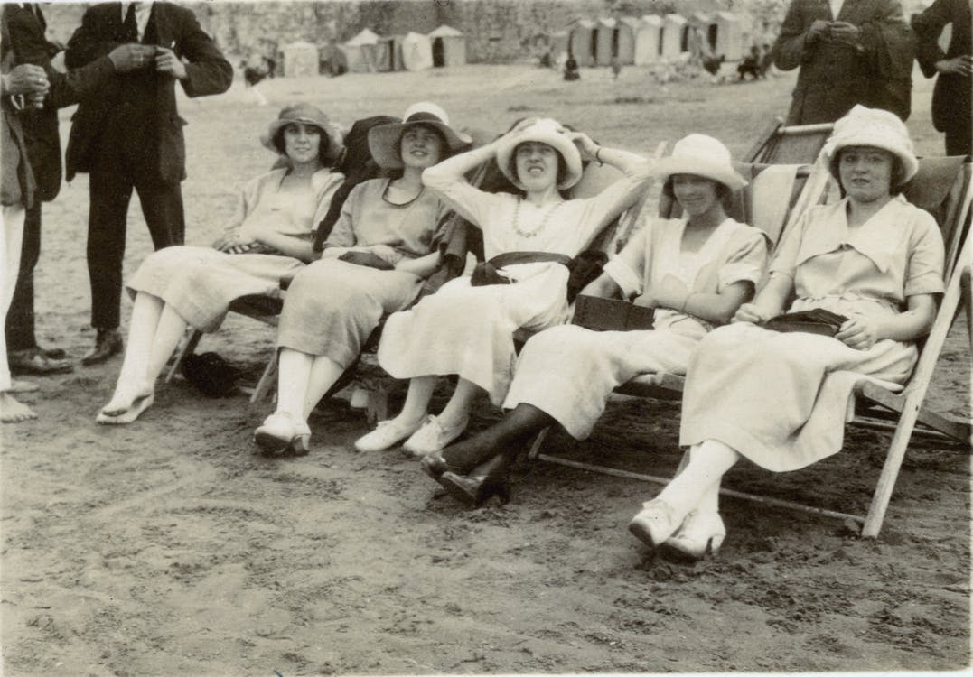 Grayscale Photo of  Women Sitting on A Folding Chair