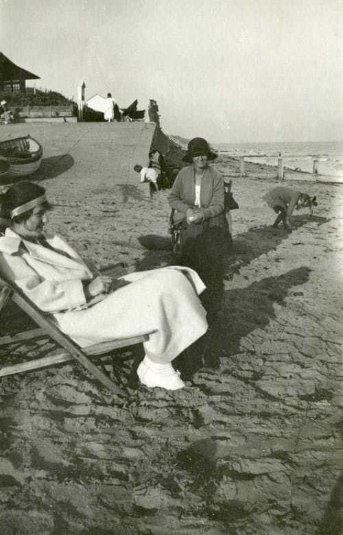 Grayscale Photo of Two Women Sitting on Folding Chairs on Beach
