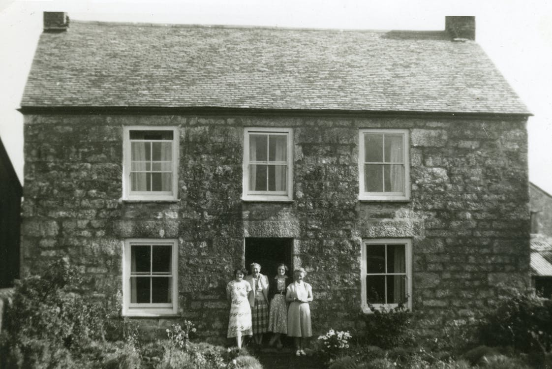 Grayscale Photo of Four Women Standing in Front of House