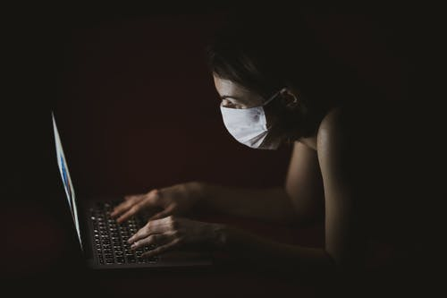 Woman Wearing Face Mask Using Macbook Pro