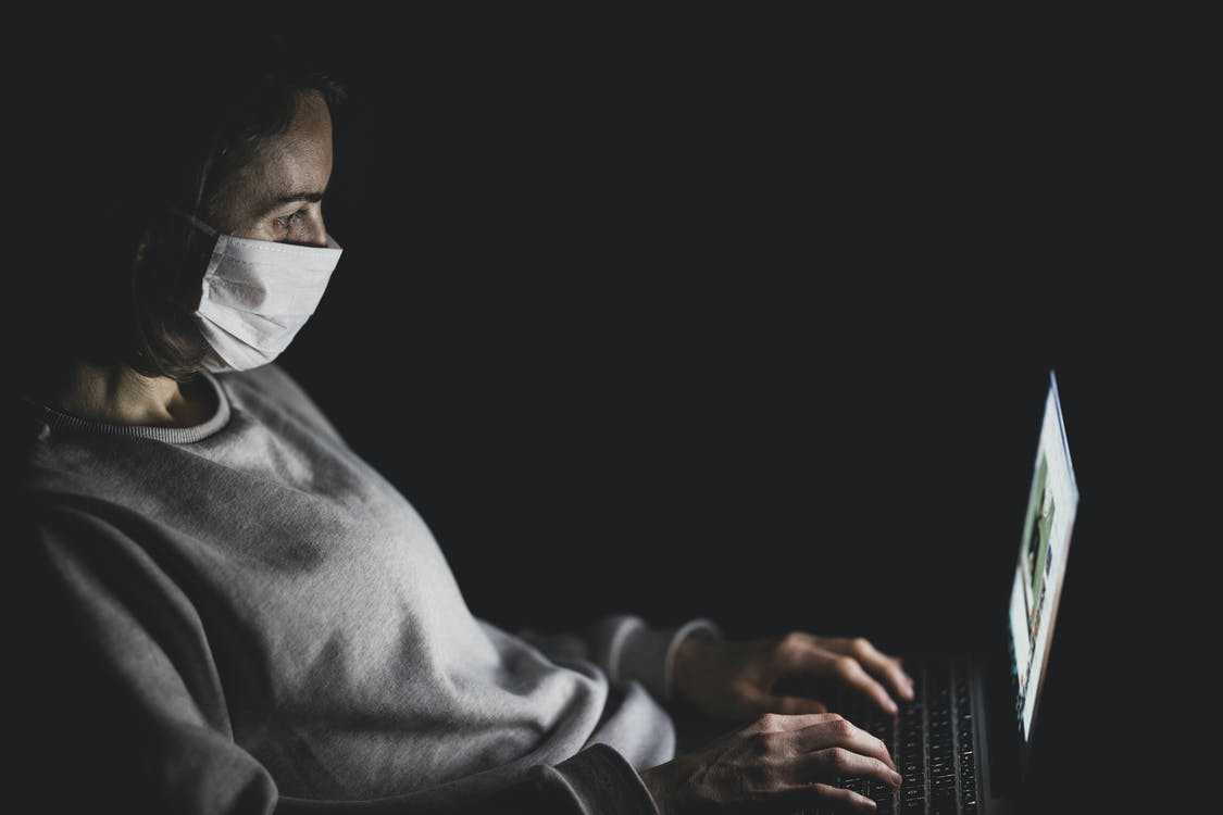 Woman Wearing Face Mask Using Black Laptop Computer