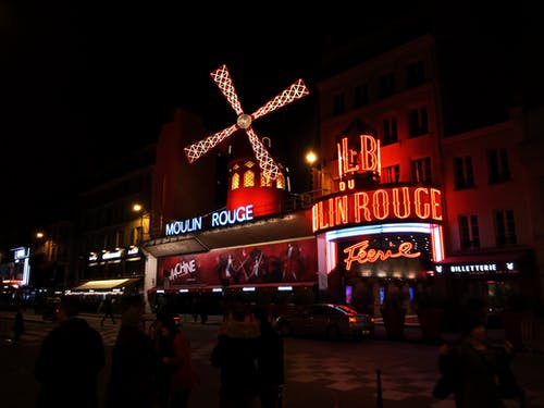 Exterior of famous cabaret club with glowing neon light illumination and banners decorate with luminous mill and located on street of Paris at night