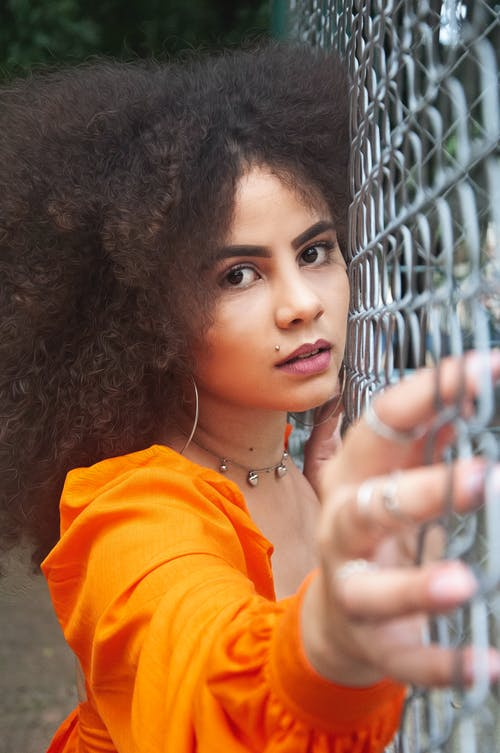 Pensive young ethnic woman standing on street behind mesh fence