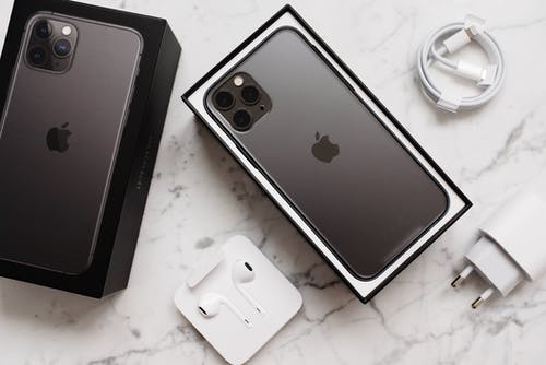 From above composition of black smartphone in box and box top and usb wire and wireless earphones on marble surface