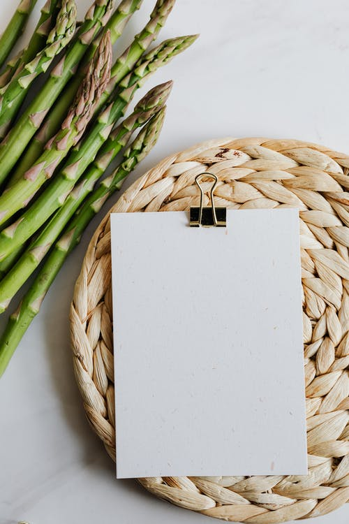 Asparagus And Blank Paper On Table