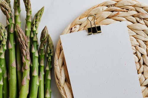 Paper sheets fastened by paper clip and asparagus