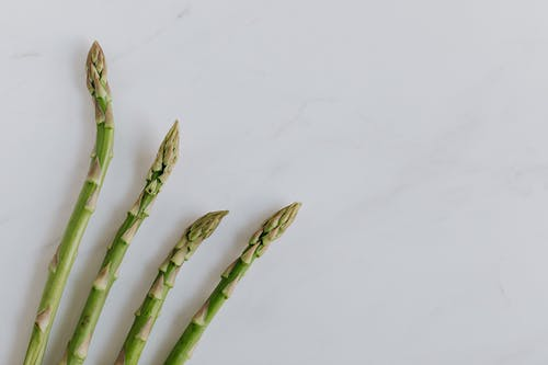 Four Stalks Of Asparagus On Marble Surface