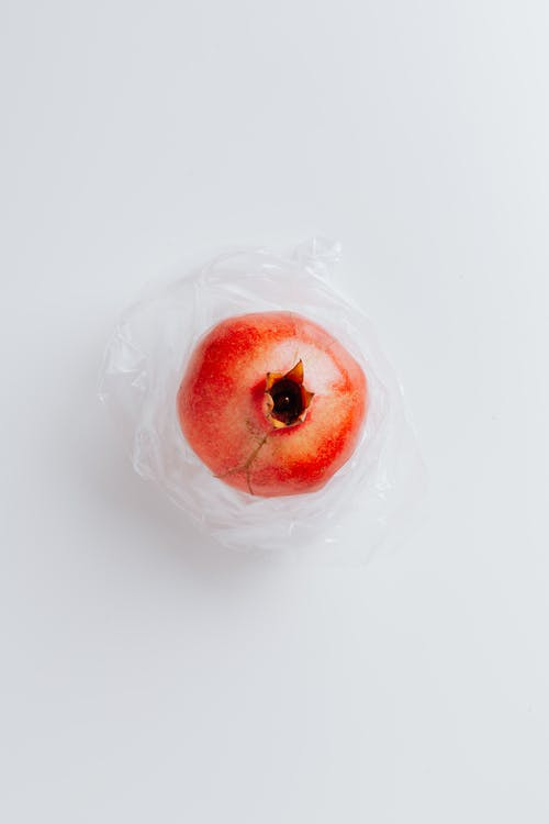 Ripe pomegranate on polyethylene bag on gray background