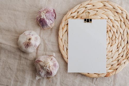 Garlic and blank paper over wicker placemat on white tablecloth