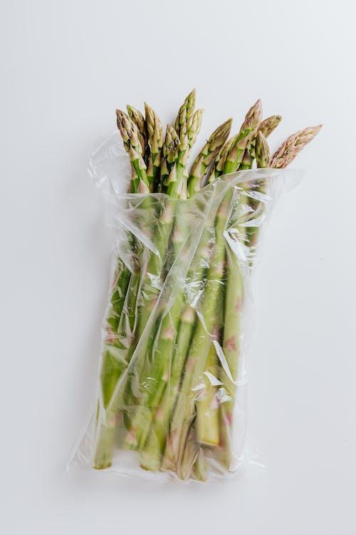 Asparagus stems in polyethylene bag isolated on white background