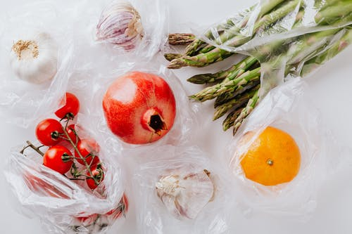 Top view of pomegranate in center surrounded by bundle of raw asparagus with orange and bunch of tomatoes put near heads of garlic in plastic bags on white surface