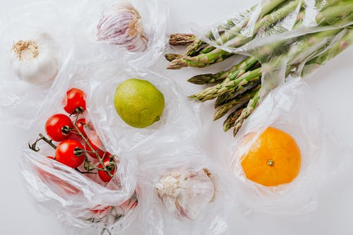 From above of bunch of tomatoes with raw asparagus put into transparent plastic bags on white table near citrus fruits and garlic bulbs