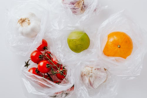 Fresh vegetables and citrus fruits put in plastic bags