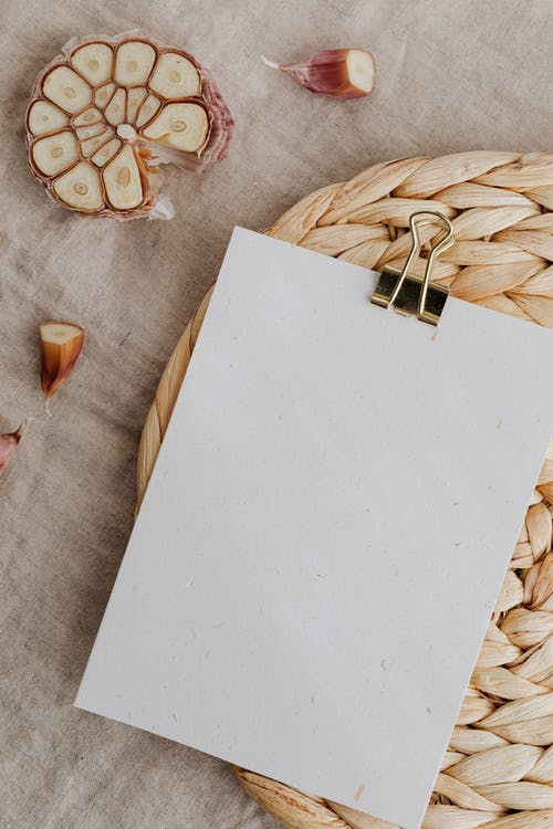 Top view of sheet of white blank paper with metal clip composed on straw table mat among cut cloves of garlic