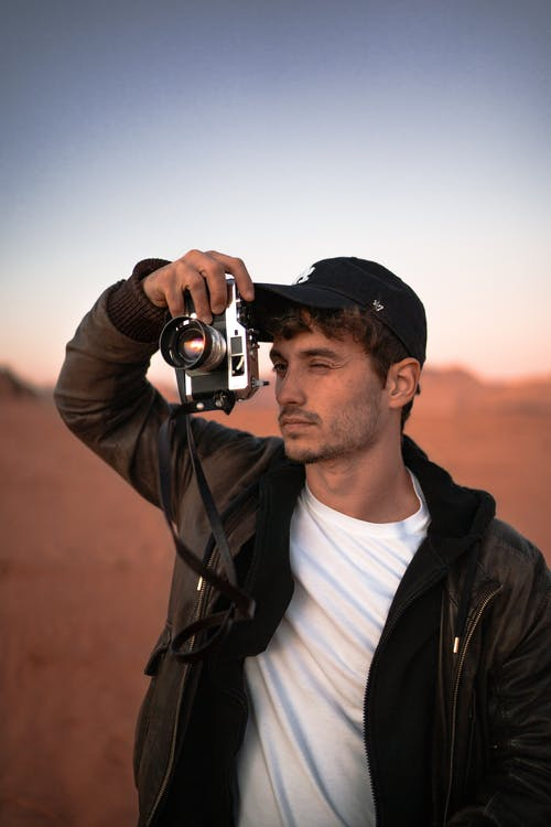 Concentrated photographer taking picture of nature in desert