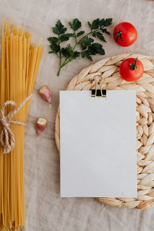 From above of blank paper with clip on wicker table mat among raw spaghetti and fresh tomatoes with parsley and cut garlic on linen surface