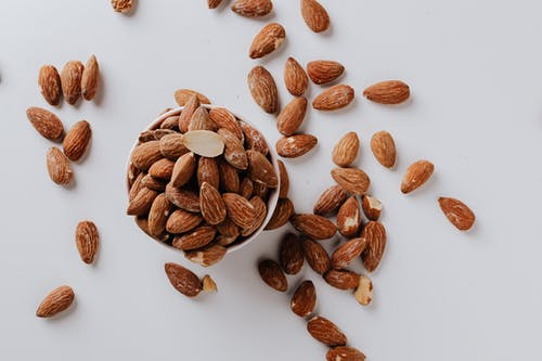 Bowl filled with raw almond nuts on white background