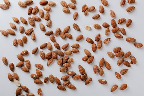 Top view of pile of delicious almond nuts cluttered on white table illustrating healthy food eating concept