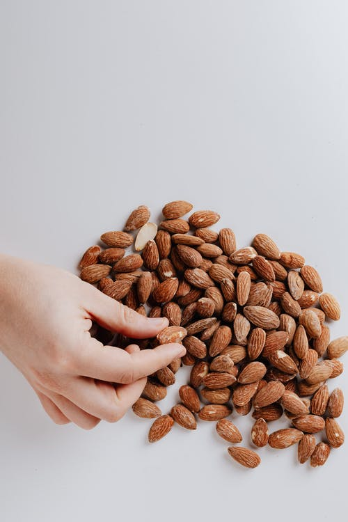 Crop person taking almond nut from white table