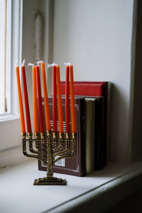 Menorah and Books Next to a Window