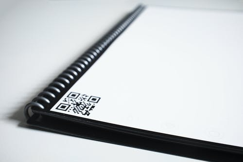 Black Spiral Notebook With Bar Code on Table
