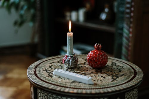 Table With a Candle and a Ceramic Pomegranate
