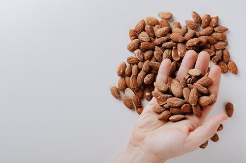 From above of anonymous male taking tasty organic almonds from pile of nuts placed on white background isolated illustrating healthy food concept