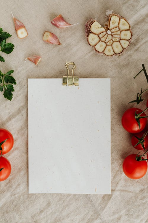 Blank clipboard with fresh vegetables and herbs on table