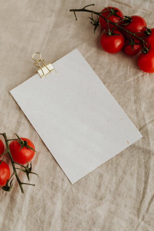 Fresh tomatoes and empty clipboard on kitchen table